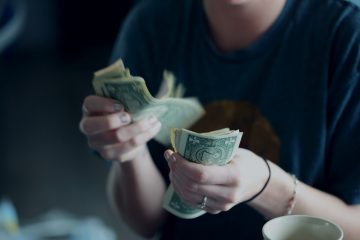 focus photography of person counting dollar banknotes